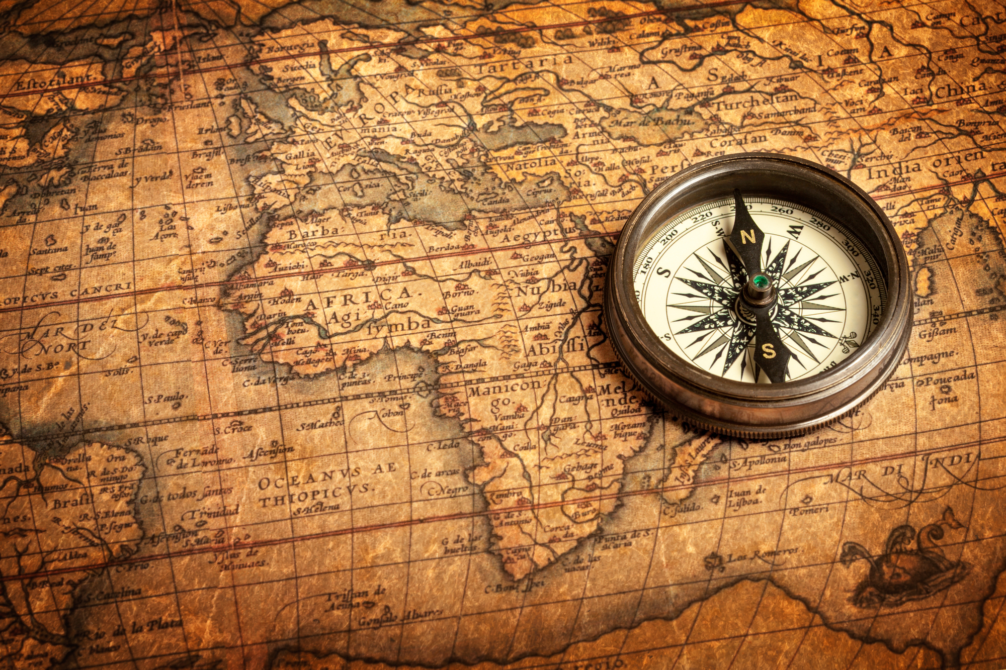 An antique compass rests on an old map of countries on planet Earth