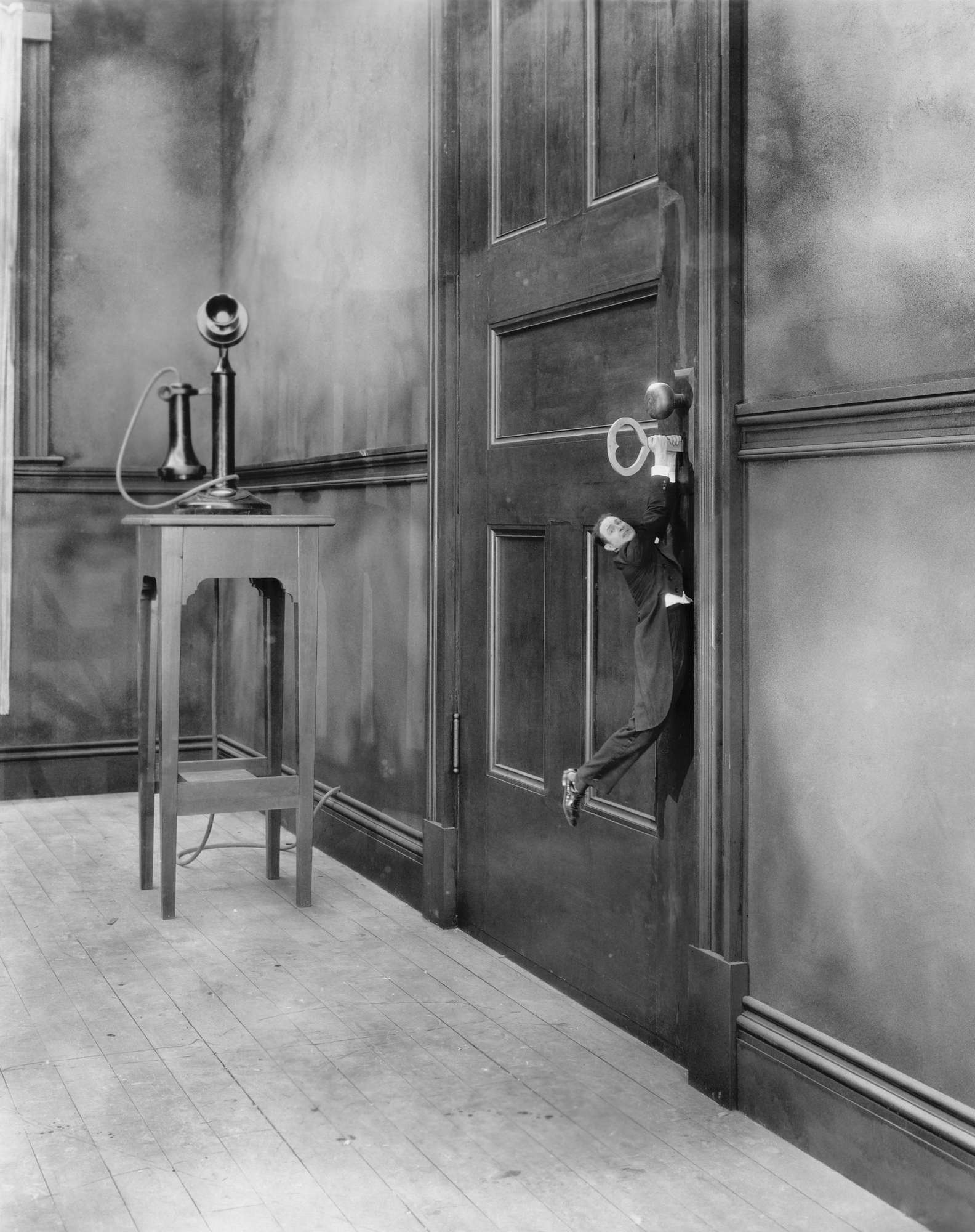 Black & White of tiny man hanging onto a key stuck in a locked door a la Alice in Wonderland