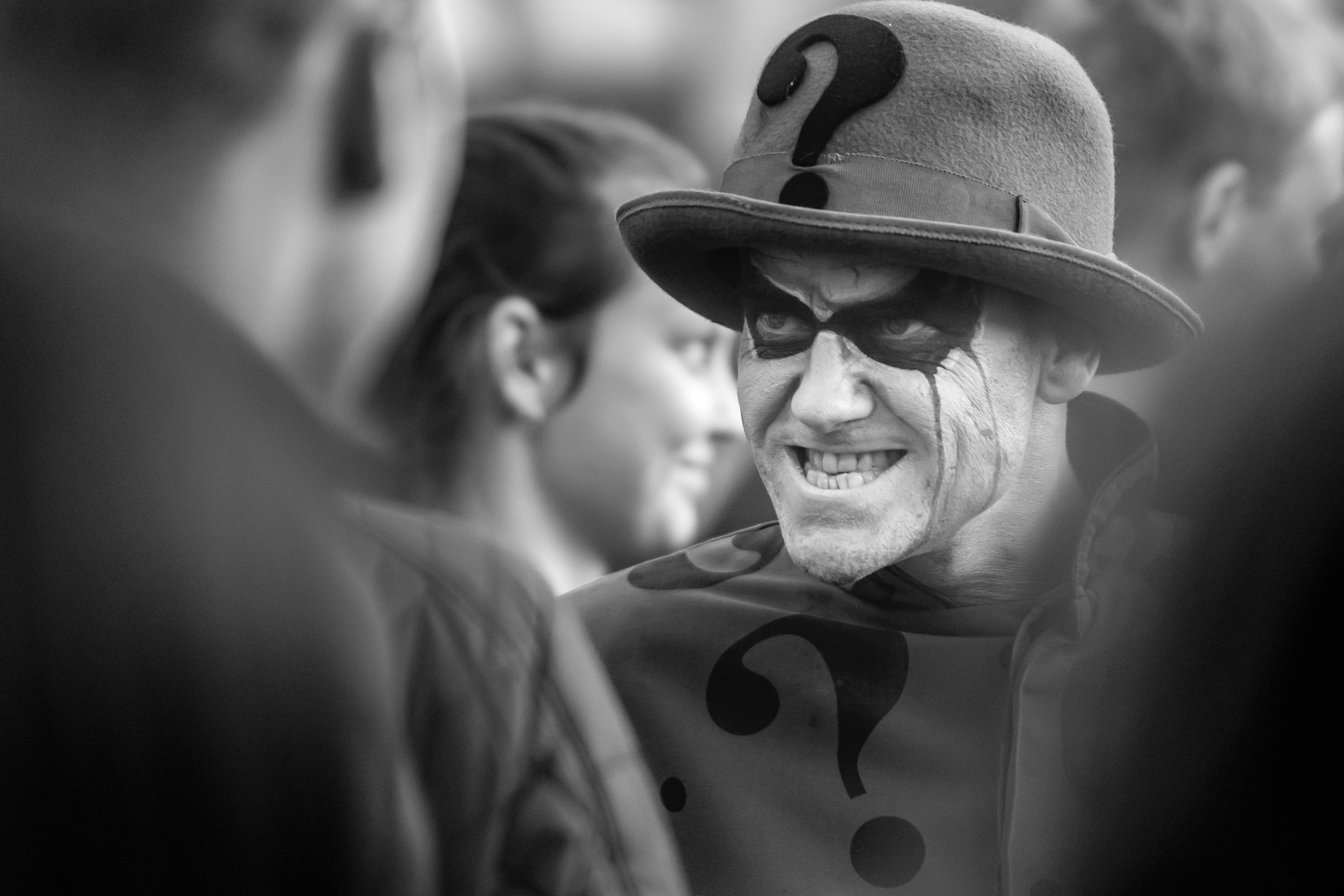 Infamous Riddler of DC Comics grins under bowler hat with large question mark in front.