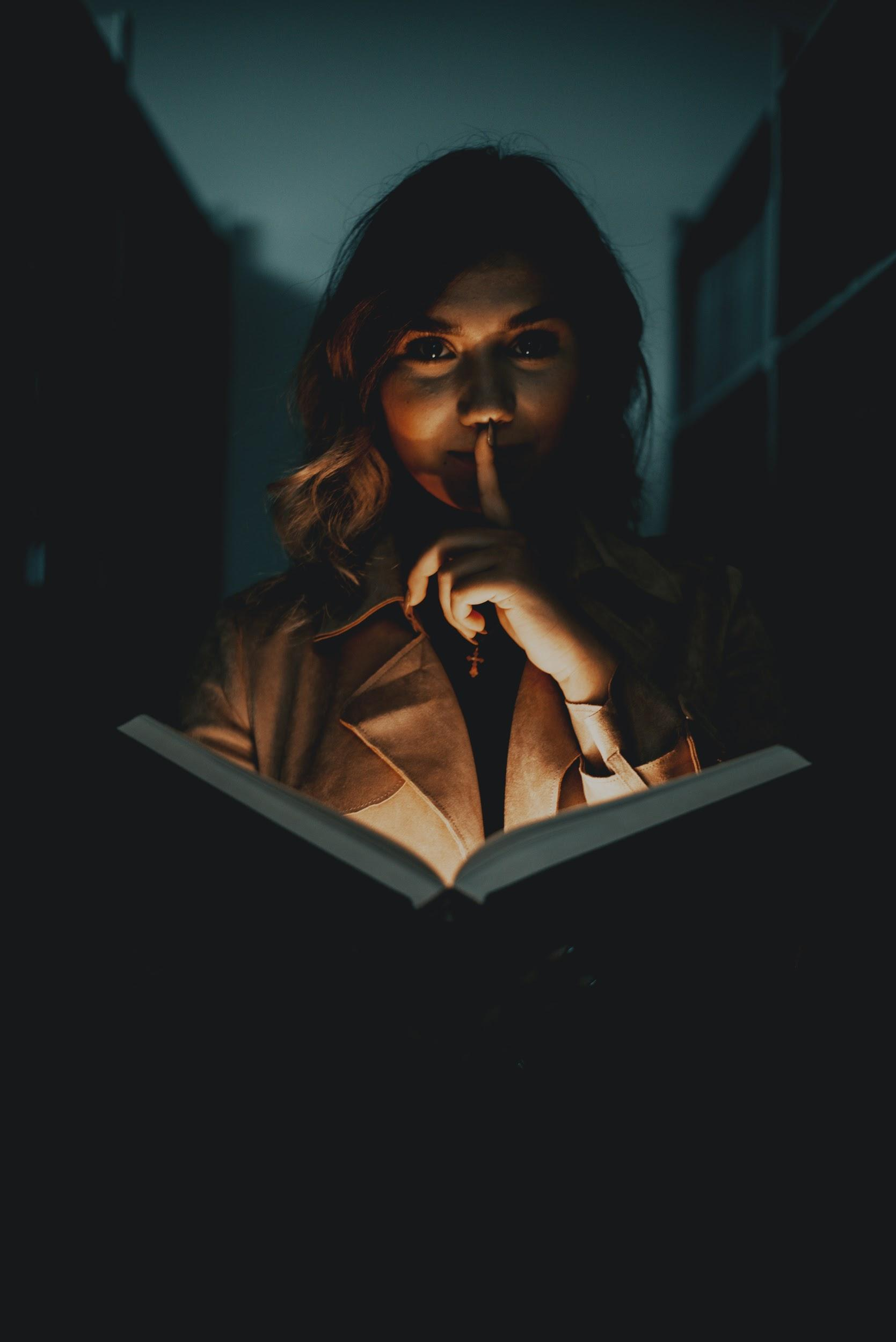 Girl with shining book in a dark library