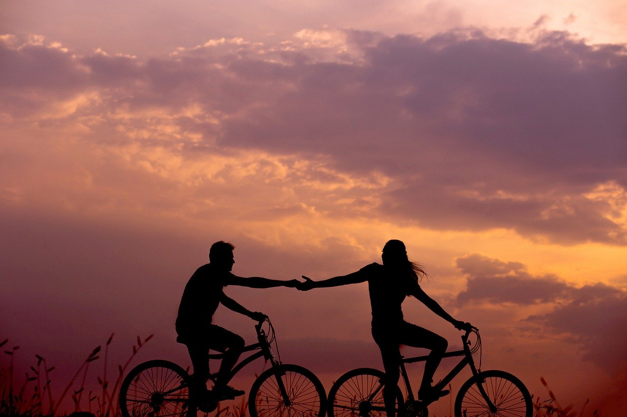 Bicycle riding couple's silhouette in the sunset