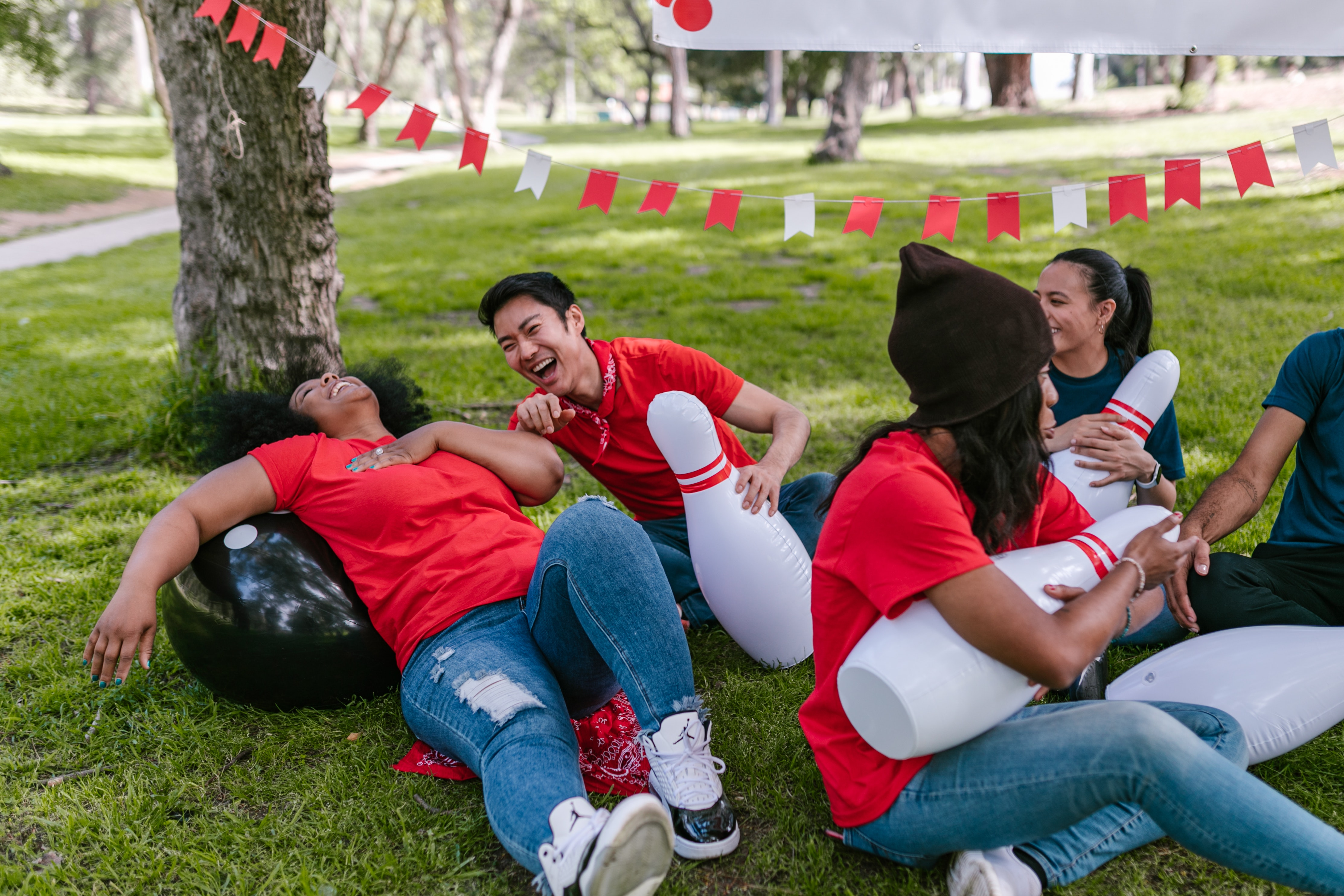 A group of people sitting on the grass laughing.
