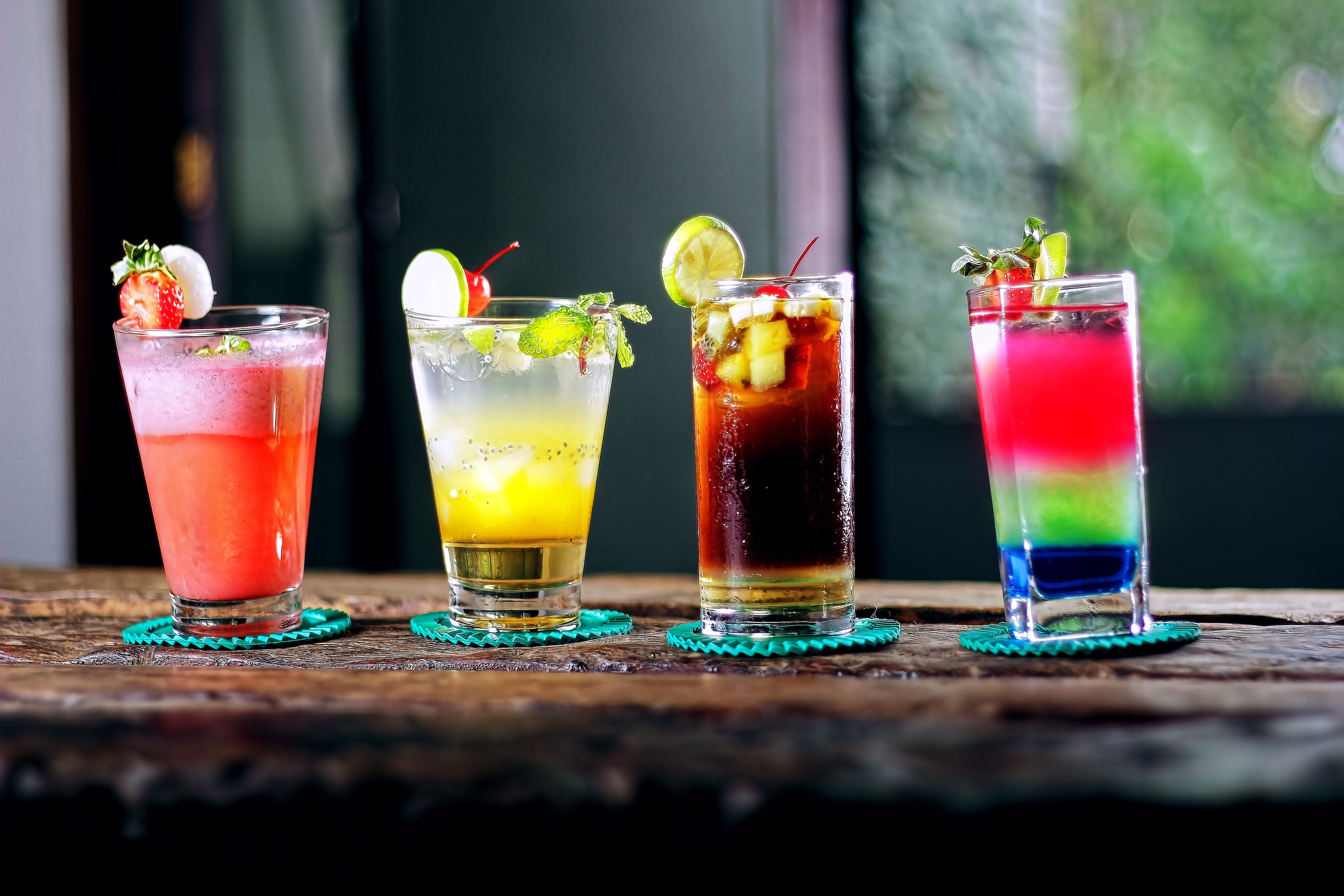4 glasses of different drinks served on a wooden table.