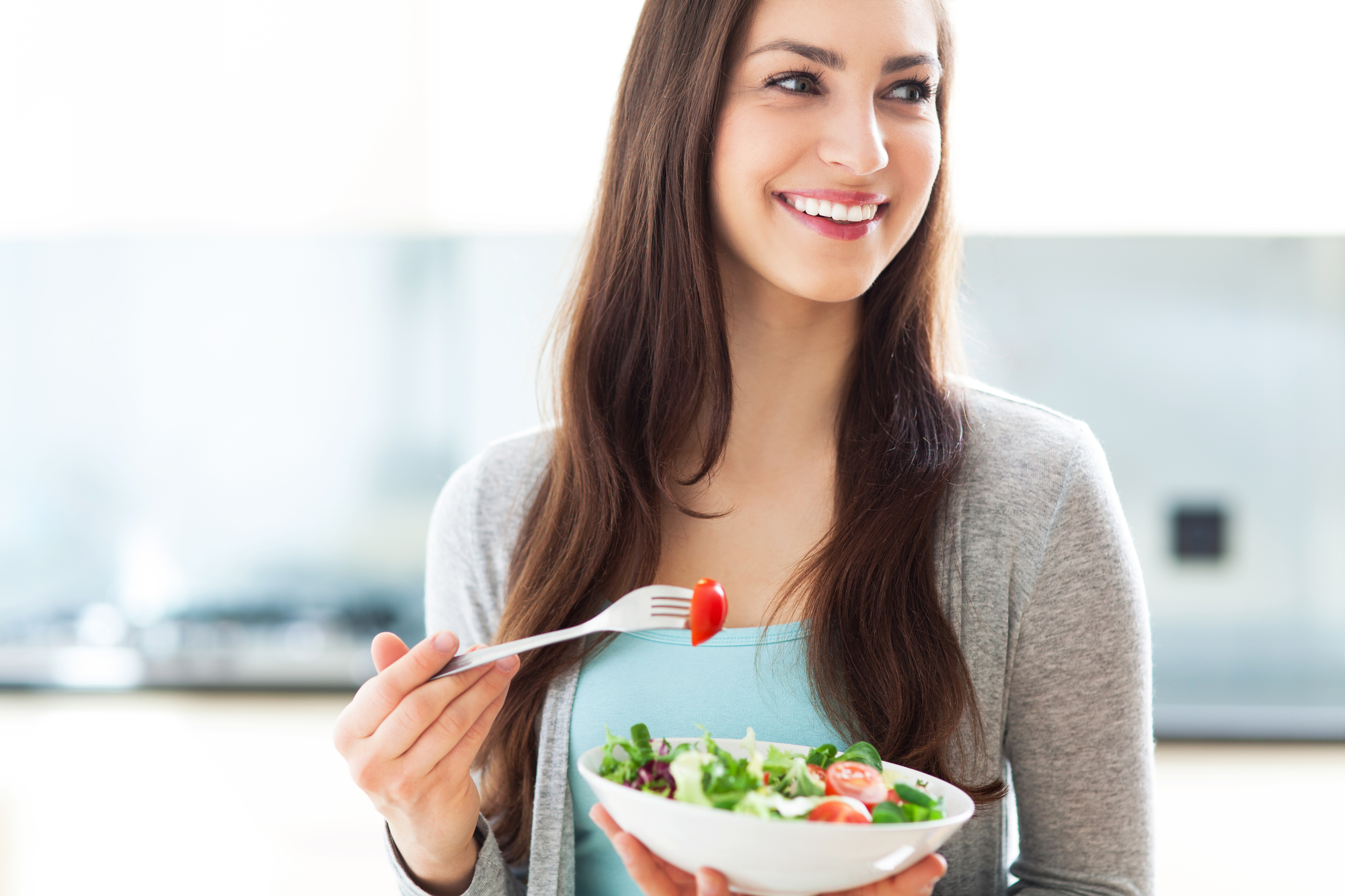 A woman looking happy and not stressed out while eating a healthy snack.