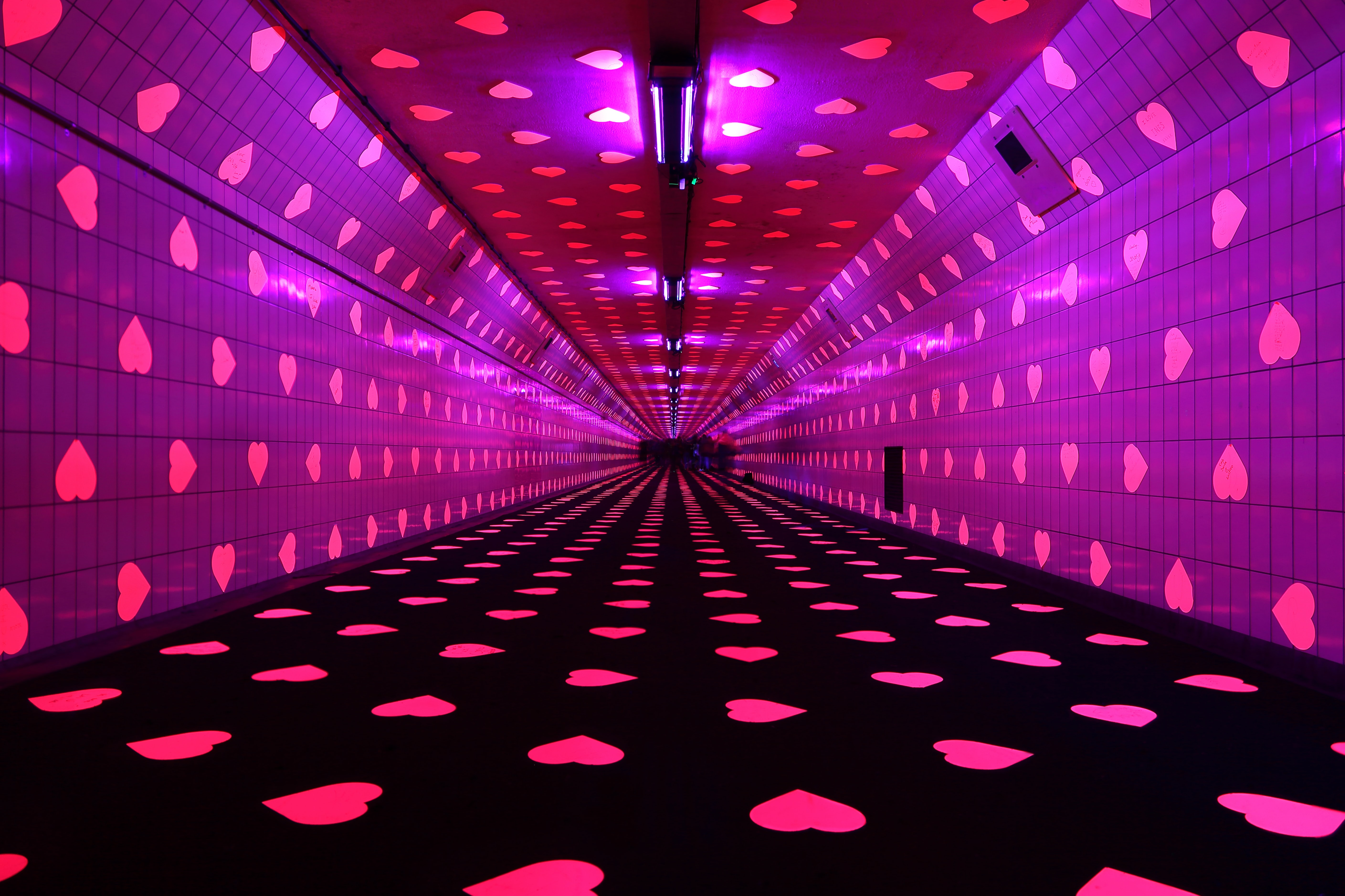 Dark tunnel with pink hearts on the wall