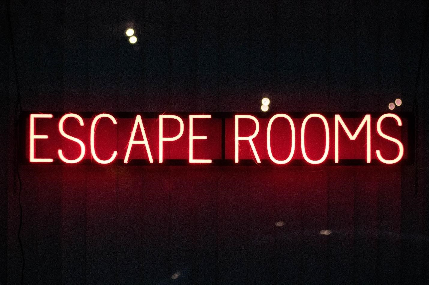 A wall lit with neon style text reading Escape Room