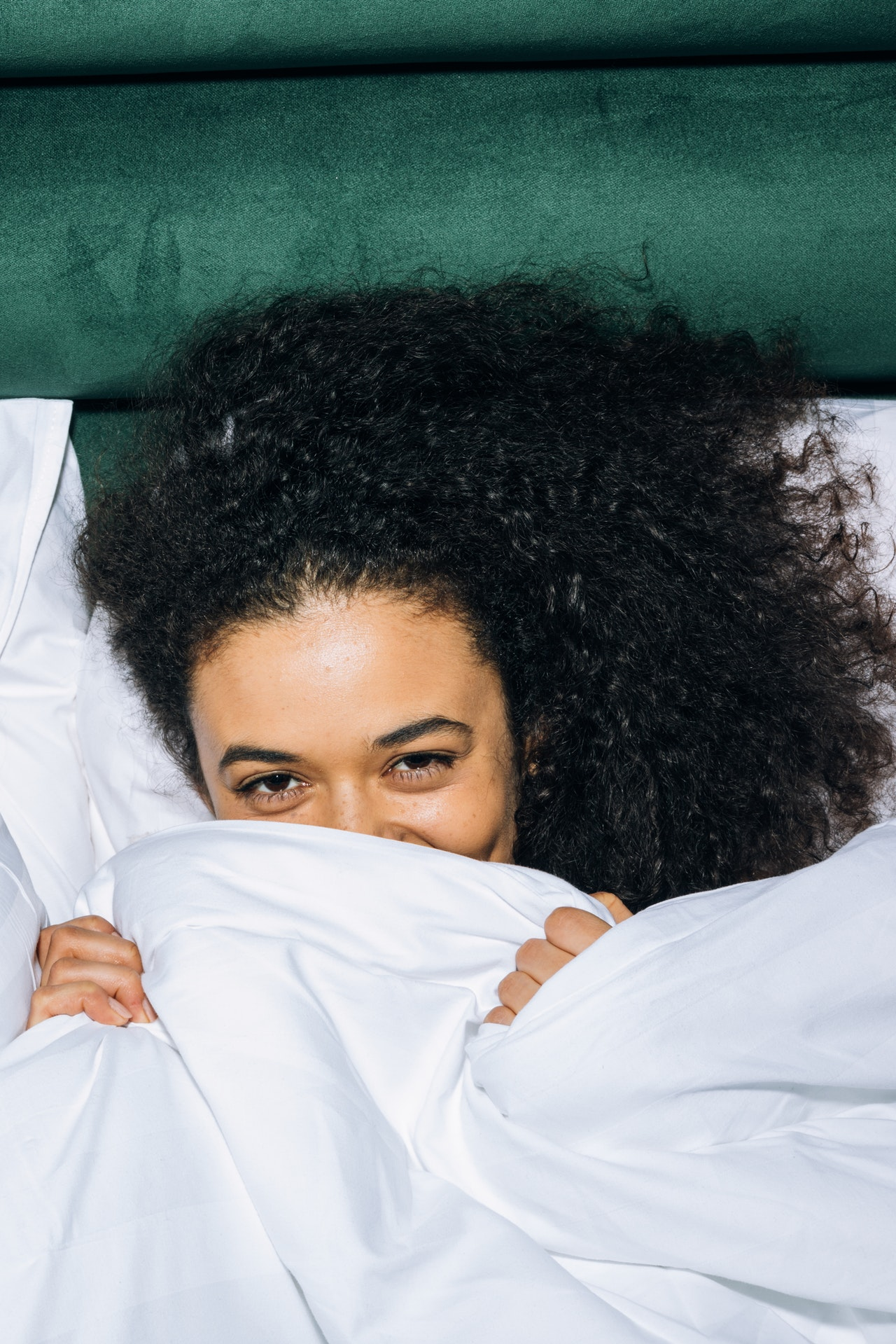 Smiling eyes of a girl with curly hair from under a blanket
