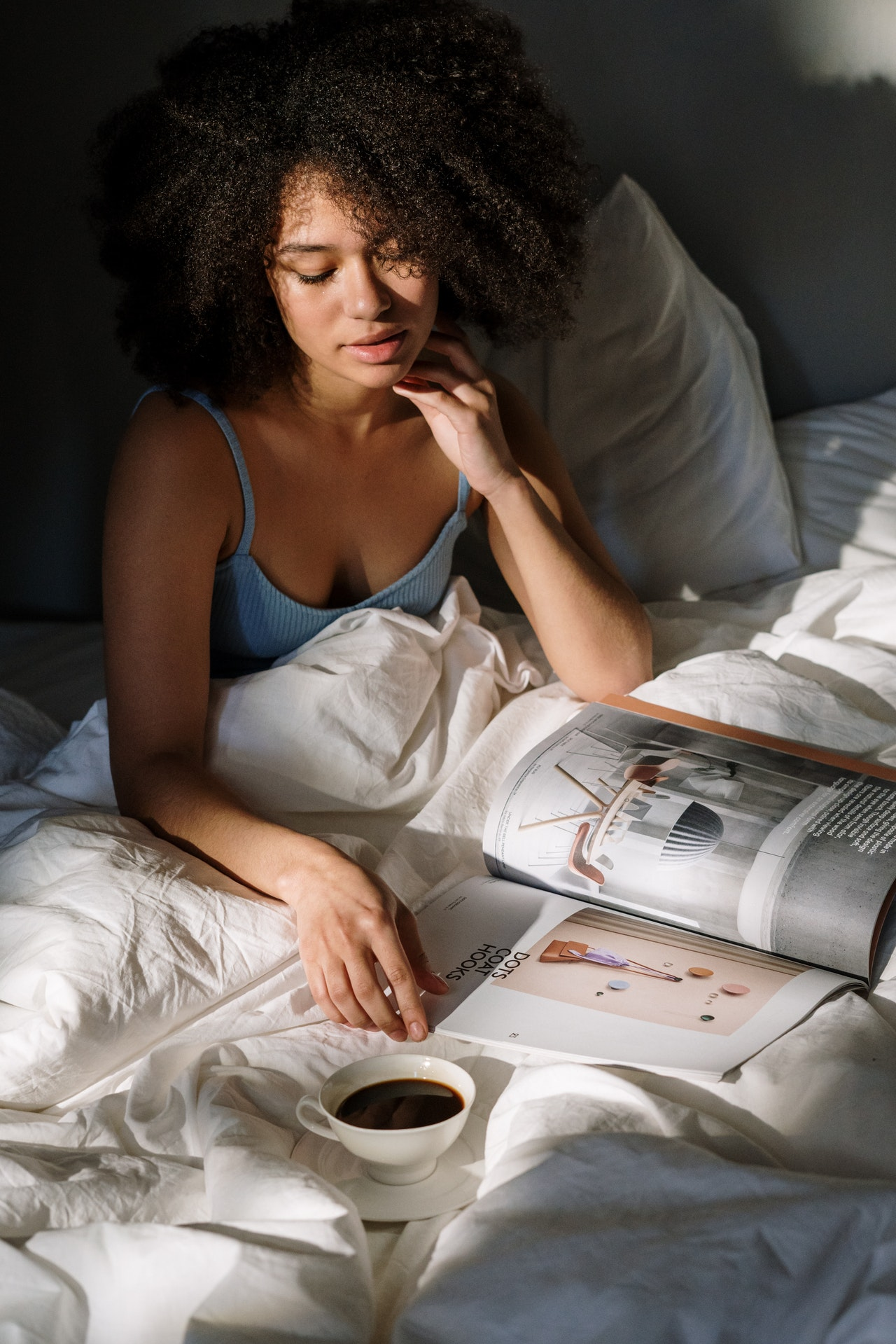 Girl with curly, black hair reading magazine with a cup of coffee in a bed in relaxing mood