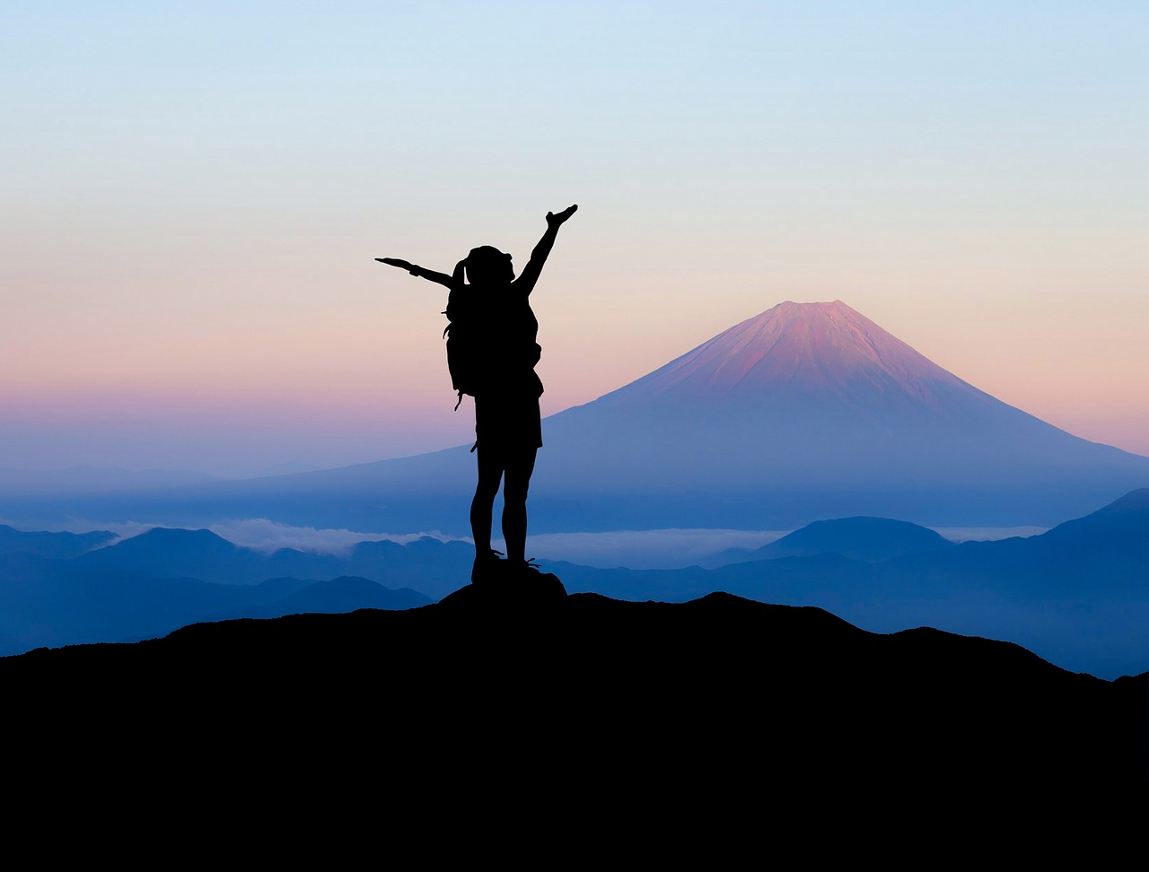 Silhouette of a girl at the top of the mountain
