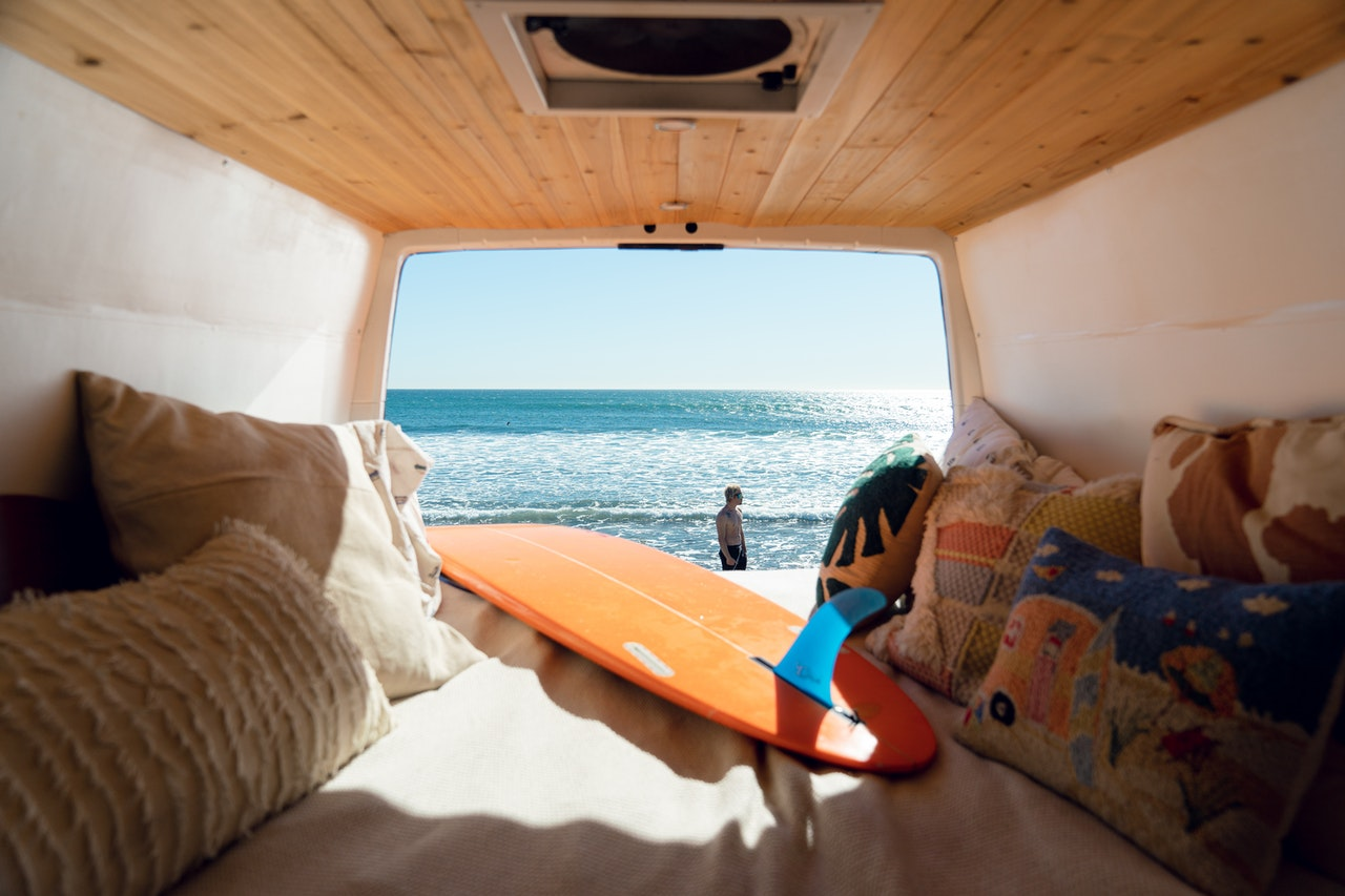 A surfboard in the back of the van facing the water.
