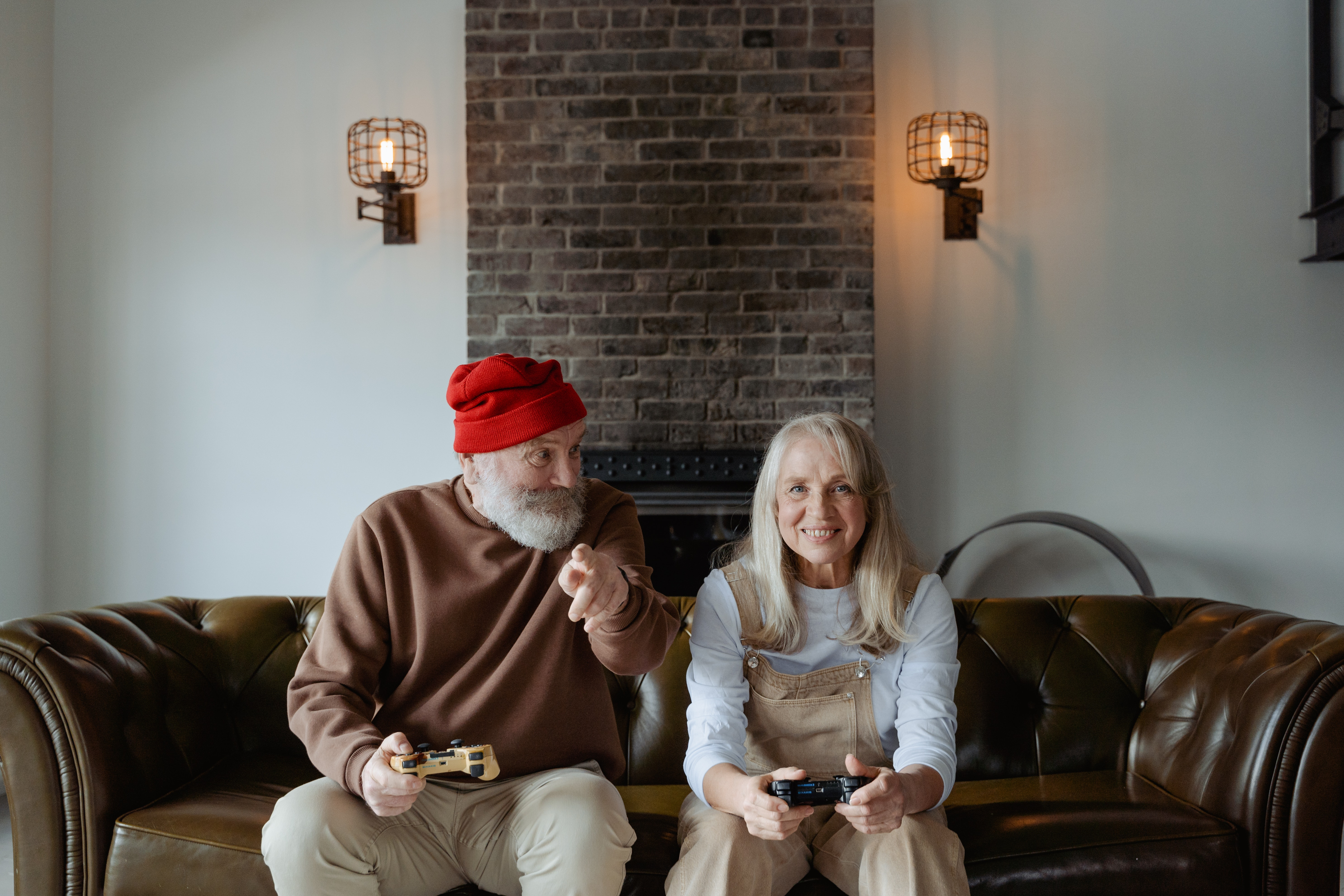 Elderly couple gaming on couch man in red beanie