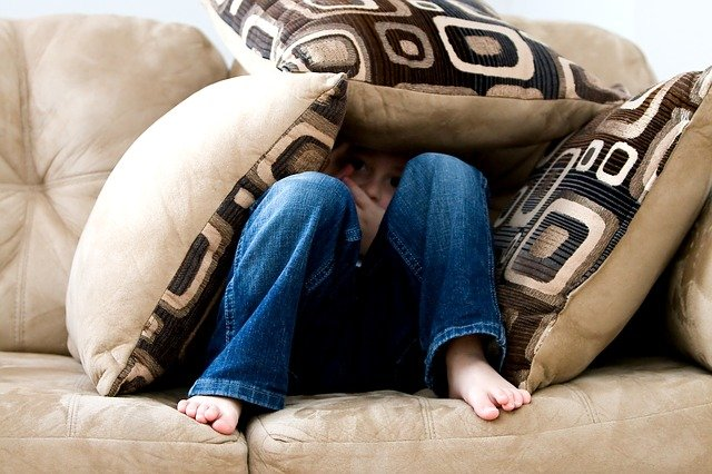 Little boy fearful under a shelter made from pillows