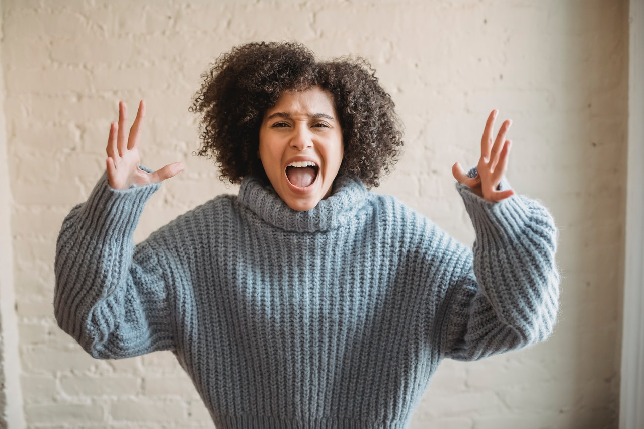 Angry girl in grey sweater shouting