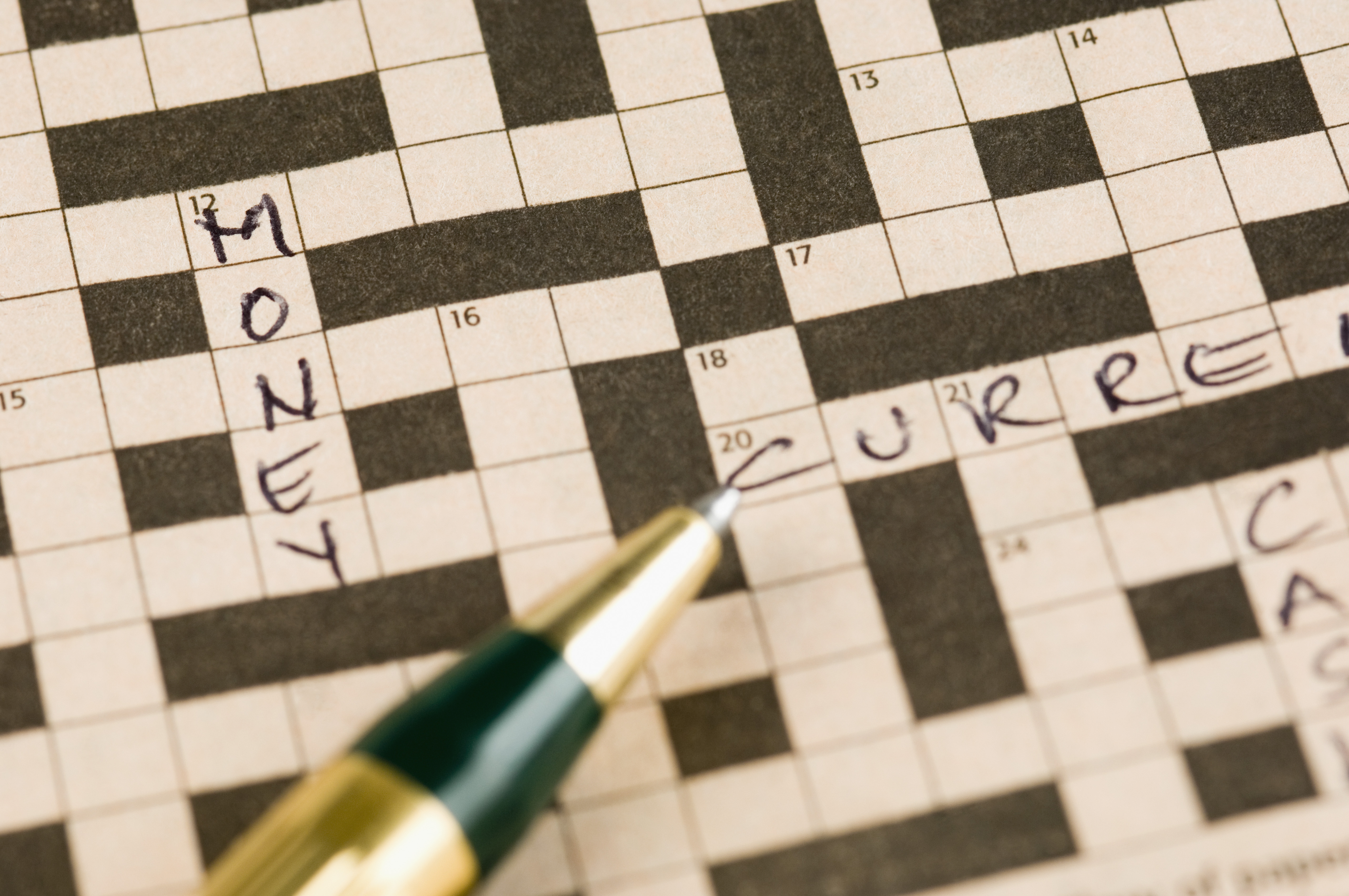 "A pen poised over a crossword puzzle missing most answers aside from the word ""money""."