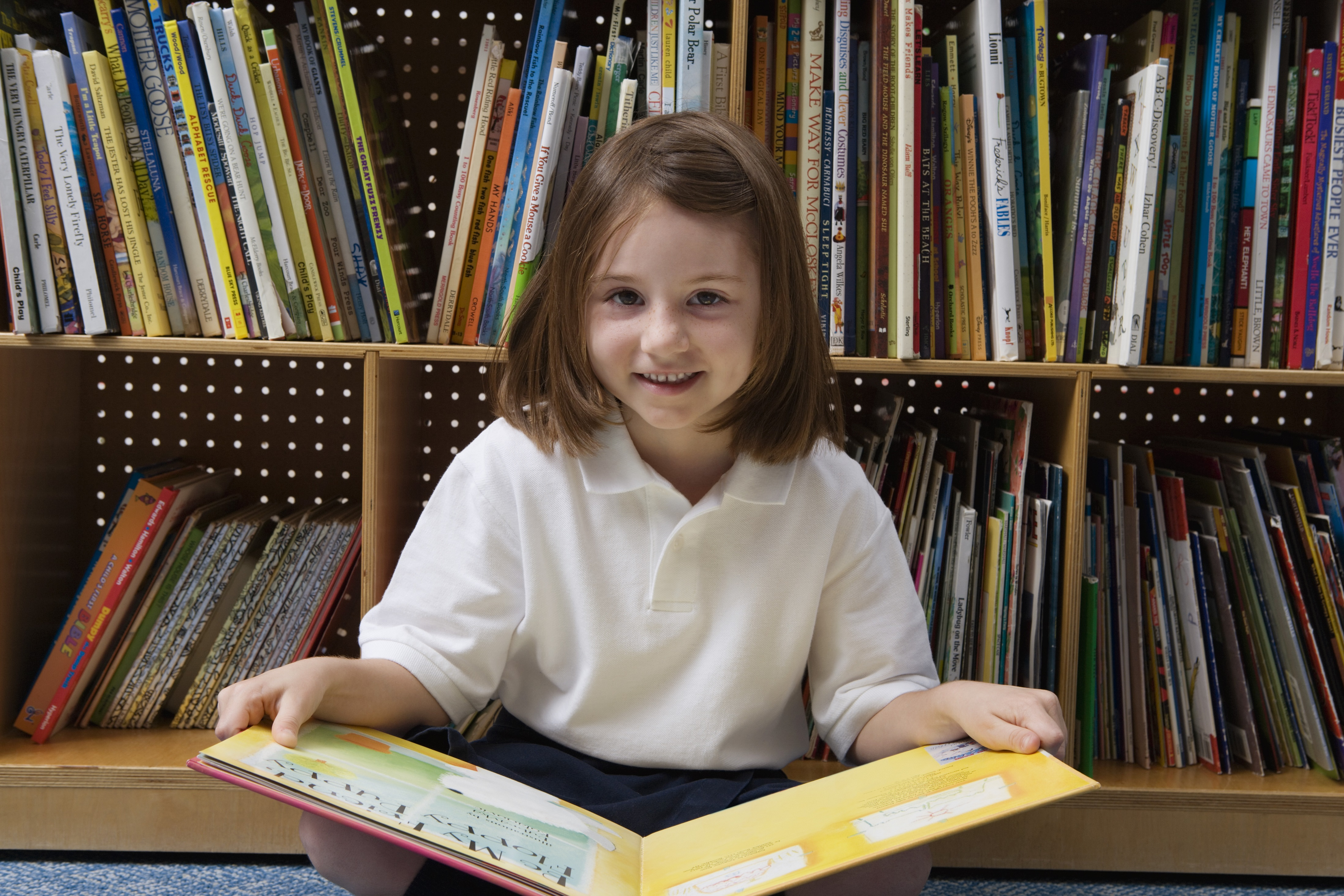 Little girl sits against a bookshelf with a book in a yellow cover open on her lap