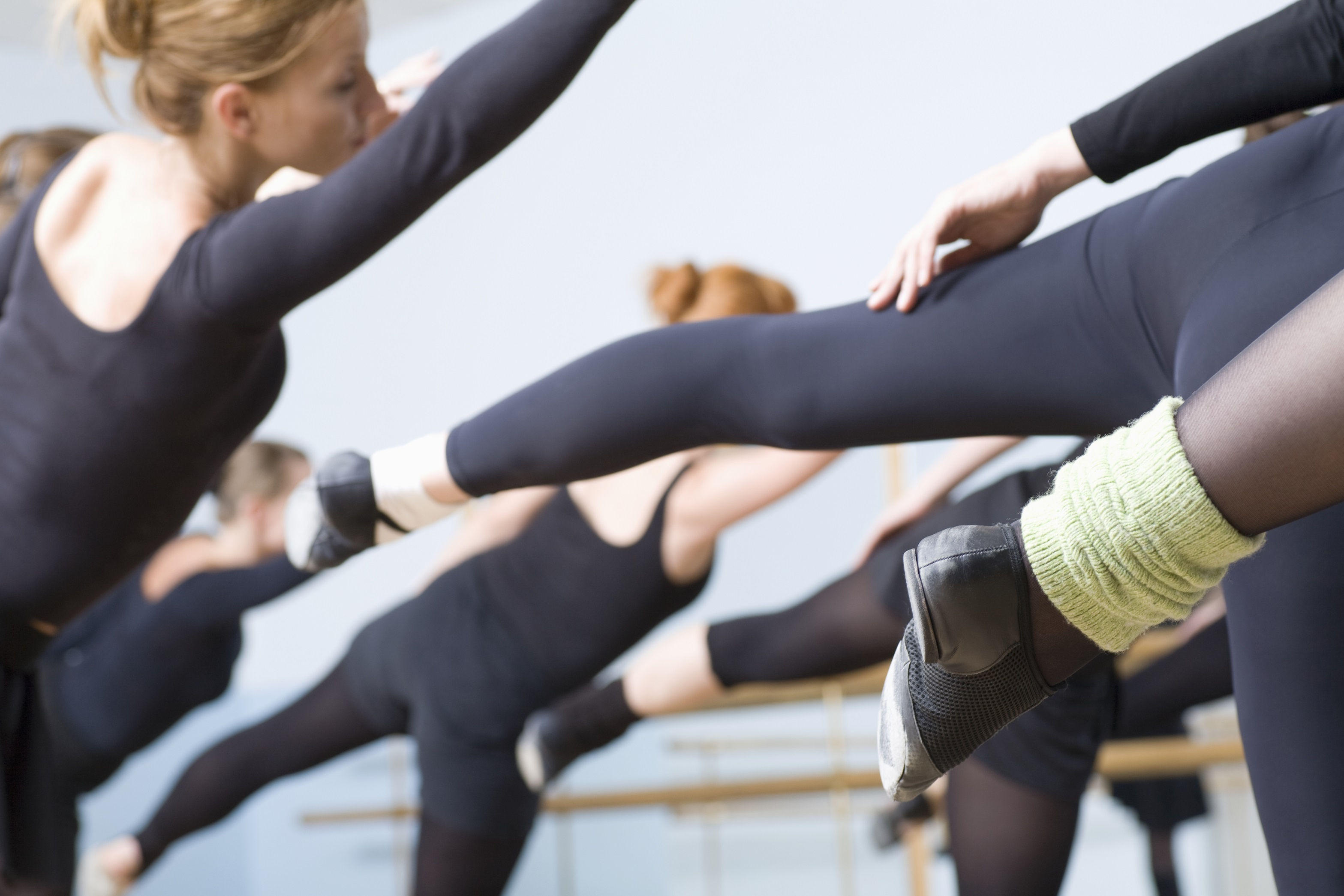 Woman and students in ballet class attire stretching in arabesque