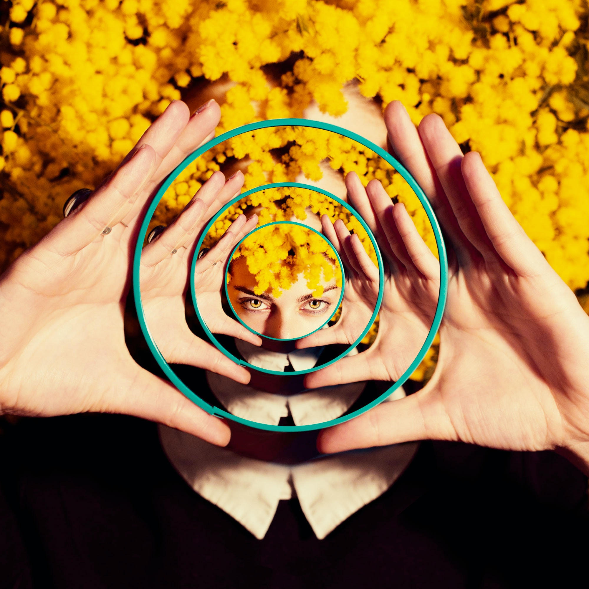 Photo of woman holding a mirror in front of yellow flowers